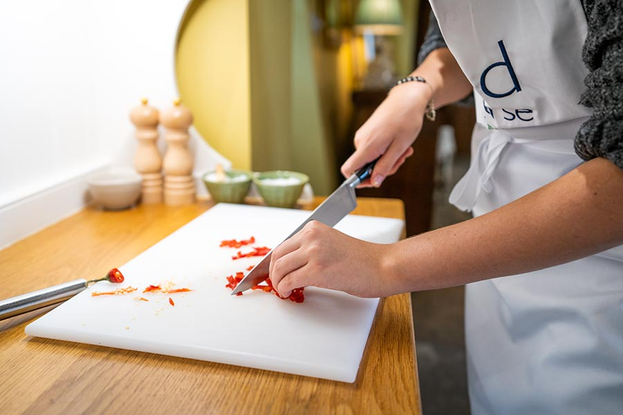Close up of young man chopping up a chilli pepper on a white chopping board