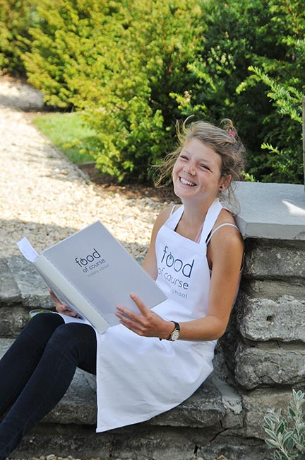 A young cookery school student laughing whilst studying for the course