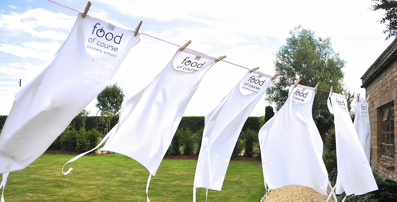 Food of Course aprons hanging on the washing line