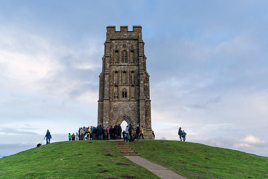St Michael's Tower on Glastonbury Tor with a crowd of people around it.